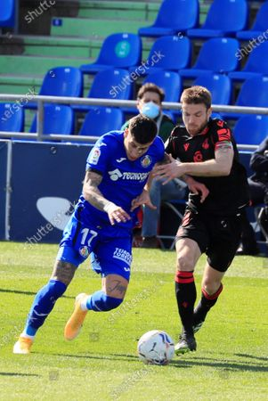 Getafe FC's Uruguayan defender Mathias Olivera (L) fights for the ball with midfielder Asier Illarramendi (R) of Real Sociedad during their LaLiga soccer match played at Coliseum Alfonso Perez in Getafe, Marid, Spain on 14 February 2021.