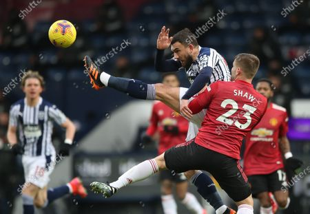 Robert Snodgrass (C) of West Bromwich in action against Luke Shaw (R) of Manchester United during the English Premier League soccer match between West Bromwich Albion and Manchester United in West Bromwich, Britain, 14 February 2021.