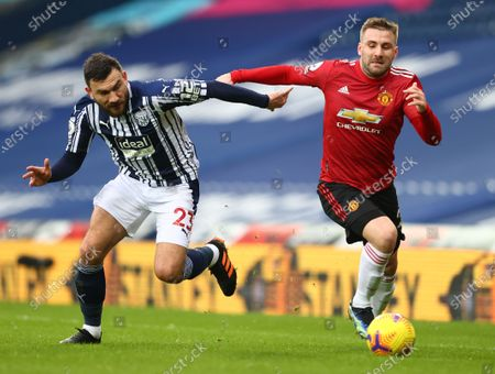 Stock Image of Robert Snodgrass (L) of West Bromwich in action against Luke Shaw (R) of Manchester United during the English Premier League soccer match between West Bromwich Albion and Manchester United in West Bromwich, Britain, 14 February 2021.