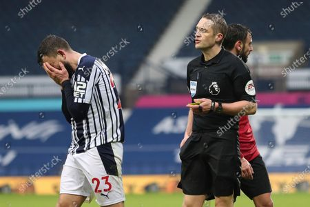 West Bromwich Albion's Robert Snodgrass, left, gestures as referee Craig Pawson shows him a yellow card during the English Premier League soccer match between West Bromwich Albion and Manchester United at the Hawthorns stadium in West Bromwich, England