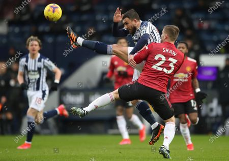 Manchester United's Luke Shaw, right, fights for the ball with West Bromwich Albion's Robert Snodgrass during the English Premier League soccer match between West Bromwich Albion and Manchester United at the Hawthorns stadium in West Bromwich, England