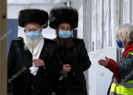 Two men from the Haredi Orthodox Jewish community arrive at an event to encourage vaccine uptake in the ultra-Orthodox community at the John Scott Vaccination Centre in London, . In hopes of breaking down barriers that sometimes isolate the Orthodox from wider society, community leaders organized the pop-up vaccination event for Saturday night to coincide with the end of Shabbat, the Jewish day of rest