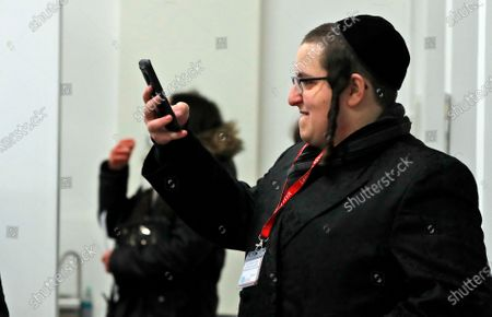 Member of the Haredi Orthodox Jewish community takes photos on his phone of an AstraZeneca vaccination at an event to encourage vaccine uptake in Britain's Haredi community at the John Scott Vaccination Centre in London, . In hopes of breaking down barriers that sometimes isolate the Orthodox from wider society, community leaders organized the pop-up vaccination event for Saturday night to coincide with the end of Shabbat, the Jewish day of rest