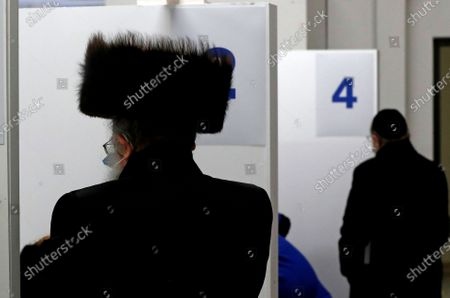 Members of the Haredi Orthodox Jewish community arrive at an event to encourage vaccine uptake in Britain's Haredi community at the John Scott Vaccination Centre in London, . In hopes of breaking down barriers that sometimes isolate the Orthodox from wider society, community leaders organized the pop-up vaccination event for Saturday night to coincide with the end of Shabbat, the Jewish day of rest