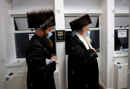 Two men from the Haredi Orthodox Jewish community arrive at an event to encourage vaccine uptake in Britain's Haredi community at the John Scott Vaccination Centre in London, . In hopes of breaking down barriers that sometimes isolate the Orthodox from wider society, community leaders organized the pop-up vaccination event for Saturday night to coincide with the end of Shabbat, the Jewish day of rest