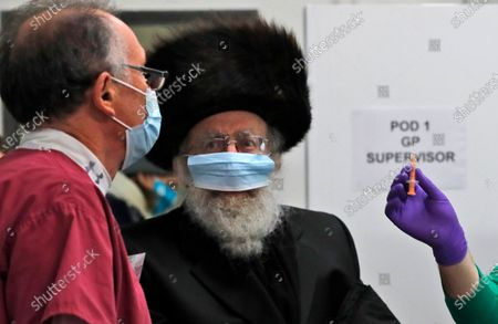 Stock Image of Nurse shows a prepared AstraZeneca coronavirus vaccine syringe to a doctor at an event to encourage vaccine uptake in Britain's Haredi Orthodox Jewish community at the John Scott Vaccination Centre in London, . In hopes of breaking down barriers that sometimes isolate the Orthodox from wider society, community leaders organized the pop-up vaccination event for Saturday night to coincide with the end of Shabbat, the Jewish day of rest