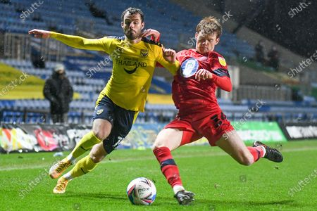 Stock Picture of Oxford United midfielder Anthony Forde (14) competes for a loss ball with Wigan Athletic defender Luke Robinson (34) during the EFL Sky Bet League 1 match between Oxford United and Wigan Athletic at the Kassam Stadium, Oxford