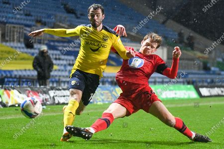 Stock Image of Oxford United midfielder Anthony Forde (14) competes for a loose  ball with Wigan Athletic defender Luke Robinson (34)during the EFL Sky Bet League 1 match between Oxford United and Wigan Athletic at the Kassam Stadium, Oxford