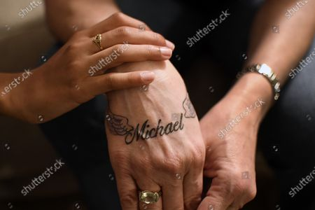 Victoria Mitchell's hand, right, bears a new tattoo with her son Michael Gregory's name as she is touched by Gregory's daughter Mikaiya Gregory Mitchell in Bridgeport, Conn. Connecticut officials are debating a statewide program of voluntary registries of people with mental health problems and disabilities to inform responding officers. Mitchell's son Michael had psychiatric problems and was shot and killed by police in 2020. Mitchell adopted Mikaiya as her daughter after her son's death