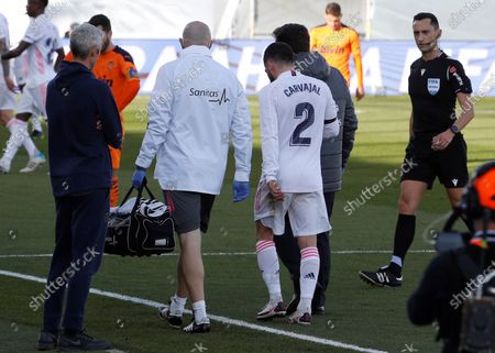 Real Madrid's midfielder Daniel Carvajal (3L) leaves the pitch accompanied by a member (2-L) of medical care team during the LaLiga game against Valencia at Alfredo Di Stefano Stadium, in Madrid, Spain, 14 February 2021.