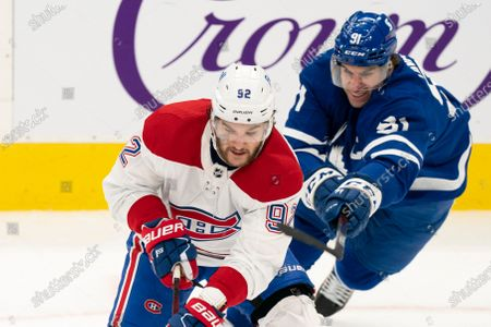 Toronto Maple Leafs center John Tavares(91) tries to hook Montreal Canadians left winger Jonathan Drouin(92) during an NHL hockey game, in Toronto, Canada