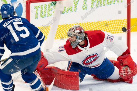 Shot from Toronto Maple Leafs center Alexander Kerfoot(15) ricochets off the post of Montreal Canadians goaltender Carey Price(31) during an NHL hockey game, in Toronto, Canada