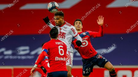 Brest's Steve Mounie heads the ball next to Lille's Benjamin Andre, right, and Lille's Jose Fonte during the French League One soccer match between Lille and Brest at the Stade Pierre Mauroy stadium in Villeneuve d'Ascq, northern France