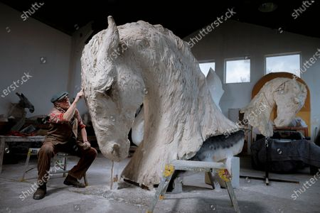 Stock Picture of Leading British sculptor, Nic Fiddian-Green working on 'Mighty Horse, a 10 foot Clay which will be cast in Bronze next week.Nic has continued to work on his monumental sculptures throughout this challenging year of lockdowns.Nic says 'Nothing stops creativity.. it's what I do'. and I count myself very lucky to have my work. The piece will be included in his 'Monumental Sculpture Walk, in the landscape around his studio in the Surrey Hills that he hopes will open to the public this spring.'The walk will take about an hour passing 18 sculptures we have placed in this beautiful landscape where I have worked and been influenced by for 28 years, the landscape breaths into my work and the horse is ever understanding and speaks calmly into my soul