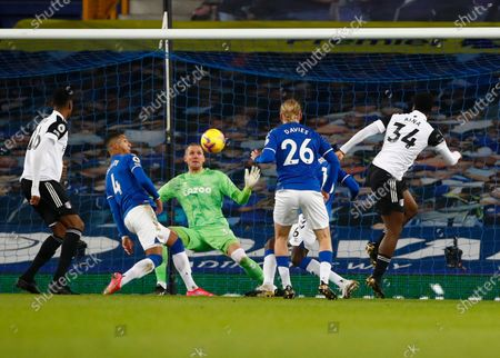 Everton's goalkeeper Robin Olsen, centre, makes a save in front of Fulham's Ola Aina, right, during the English Premier League soccer match between Everton and Fulham at Goodison Park in Liverpool, England