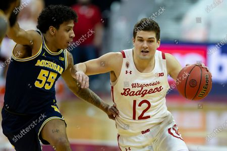 Wisconsin Badgers guard Trevor Anderson #12 drives past Michigan Wolverines guard Eli Brooks #55 during the NCAA basketball game between the Michigan Wolverines and the Wisconsin Badgers at the Kohl Center in Madison, WI