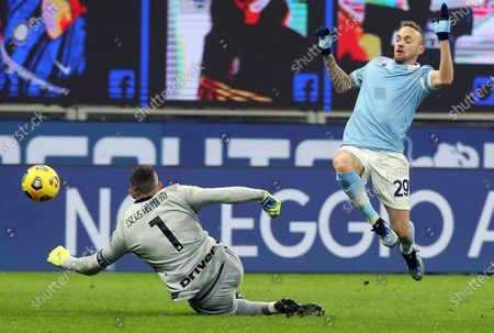 Inter Milan's goalkeeper Samir Handanovic (L) challenges for the ball Lazio's Manuel Lazzari during the Italian Serie A soccer match between FC Inter and SS Lazio at Giuseppe Meazza stadium in Milan, Italy, 14 February 2021.