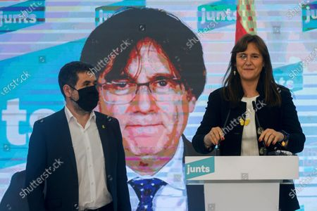 Catalan pro-independence party Junts per Catalunya (JxCat)'s presidential candidate Laura Borras (C) accompanied via videoconference by former Catalan President Carles Puigdemont (on screen) and JxCat's leader Jordi Sanchez (L) addresses a press conference after a meeting to analyze the first election results by the party at Hotel Barcelo Sants in Barcelona, Catalonia, north-eastern Spain, after the Catalonian regional elections, 14 February 2021.