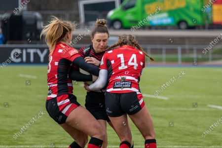 Sarah Mckenna (#15 Saracens Women) stopped by Millie Wood (#13 Gloucester-Hartpury Women) and Kelly Smith (#14 Gloucester-Hartpury Women)