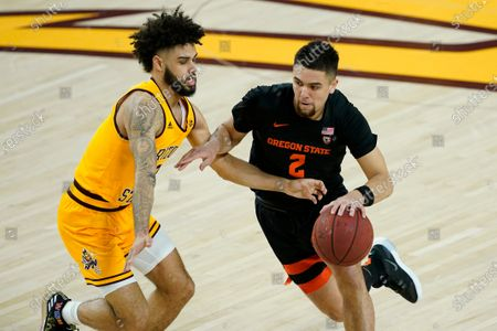 Stock Image of Oregon State guard Jarod Lucas (2) drives as Oregon State guard Gianni Hunt defends during the first half of an NCAA College basketball game, in Tempe, Ariz