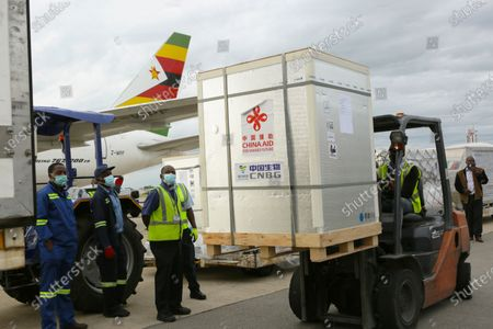 Forklift moves part of the Sinopharm COVID-19 vaccine from China upon arrival at Robert Mugabe International airport in Harare, . Zimbabwe has received its first COVID-19 vaccines with the arrival early Monday of an Air Zimbabwe jet carrying 200,000 Sinopharm doses from China