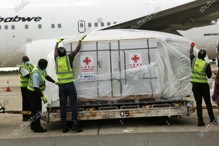 Airport handling staff unwrap part of the Sinopharm COVID-19 vaccine from China upon arrival at Robert Mugabe International airport in Harare, . Zimbabwe has received its first COVID-19 vaccines with the arrival early Monday of an Air Zimbabwe jet carrying 200,000 Sinopharm doses from China