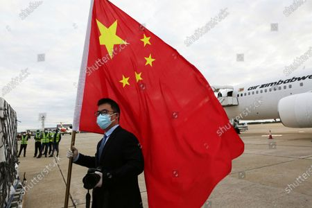 An official from the Chinese Embassy in Zimbabwe holds a Chinese flag next to a plane carrying Sinopharm COVID-19 vaccine from China upon arrival at Robert Mugabe International airport in Harare, . Zimbabwe has received its first COVID-19 vaccines with the arrival early Monday of an Air Zimbabwe jet carrying 200,000 Sinopharm doses from China