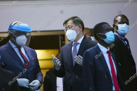 Chinese Ambassador to Zimbabwe Guo Shaochun, right, chats with Zimbabwe Deputy President Constantino Chiwenga, left, at the handover ceremony of the Sinopharm COVID-19 vaccine from China at Robert Mugabe International airport in Harare, . Zimbabwe has received its first COVID-19 vaccines with the arrival early Monday of an Air Zimbabwe jet carrying 200,000 Sinopharm doses from China