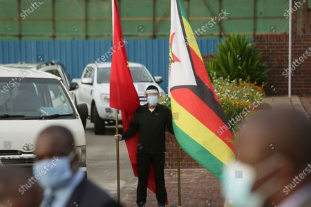 An official from the Chinese Embassy in Zimbabwe holds Chinese, left, and Zimbabwean flags after a plane carrying Sinopharm COVID-19 vaccine from China, arrived at Robert Mugabe International airport in Harare, . Zimbabwe has received its first COVID-19 vaccines with the arrival early Monday of an Air Zimbabwe jet carrying 200,000 Sinopharm doses from China