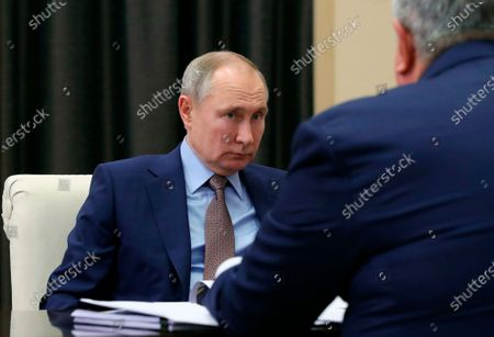 Russian President Vladimir Putin, left, listens to Russian CEO of Rosneft oil company Igor Sechin, back to a camera, during their meeting at the Novo-Ogaryovo residence outside Moscow, Russia