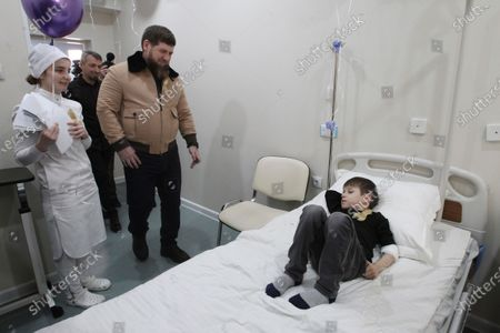 Chechnya's regional leader Ramzan Kadyrov, second left, speaks to a boy as he visits a children's cancer center in Grozny, Russia