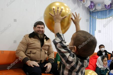 Chechnya's regional leader Ramzan Kadyrov plays a ball with a boy as he visits a children's cancer center in Grozny, Russia