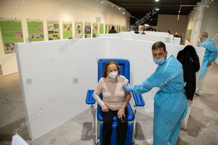 "A nurse vaccinates a patient over 80 in the new area dedicated to vaccinations in the ""Ennio Morricone"" Auditorium in Rome"