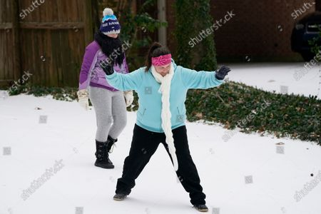 Stock Photo of Jennifer Taylor shows her daughter Amelie Taylor, 12, how to slide with style along the ice covered Jackson, Miss., street, as light snow mixed with sleet, and rain continue to cover much of the state. The National Weather Service forecasts temperatures barely hovering at 20 degrees Fahrenheit, and likely slipping into the single digits by Tuesday morning. A winter storm warning continues throughout the state