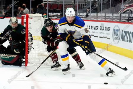 St. Louis Blues center Jacob De La Rose (61) shields the puck from Arizona Coyotes right wing Christian Fischer (36) in the third period during an NHL hockey game, in Glendale, Ariz