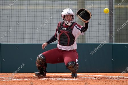New Mexico State catcher Nikki Butler catches a warmup pitch during an NCAA softball game against Liberty, in Leesburg, Fla