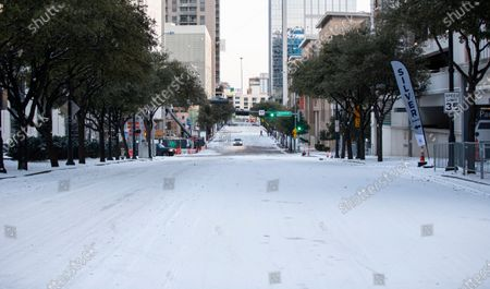 Lone vehicle drives on Victory Ave. in front of American Airlines Center which was to host the Nashville Predators and the Dallas Stars NHL hockey game, in Dallas. Dallas Mayor Eric Johnson requested that the teams not play Monday due to a shortage of electricity in the region