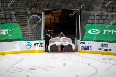 Crews remove a net from the ice at American Airlines Center which was to host the Nashville Predators and the Dallas Stars NHL hockey game, in Dallas. Dallas Mayor Eric Johnson requested that the teams not play Monday due to a shortage of electricity in the region