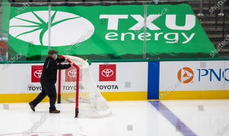 Crew member removes a net from the ice at American Airlines Center which was to host the Nashville Predators and the Dallas Stars NHL hockey game, in Dallas. Dallas Mayor Eric Johnson requested that the teams not play Monday due to a shortage of electricity in the region
