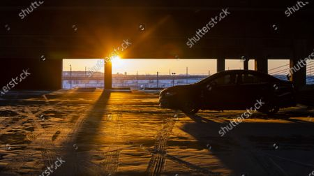 The sun sets as a lone vehicle sits in a snow-covered parking garage at American Airlines Center which was to host the Nashville Predators and the Dallas Stars NHL hockey game, in Dallas. Dallas Mayor Eric Johnson requested that the teams not play Monday due to a shortage of electricity in the region