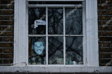 A view of an image of an American singer, Lionel Richie, and a sticker 'Hello' on a house window in Ranelagh.