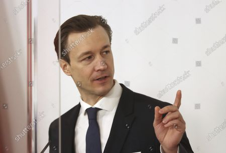 Austrian Finance Minister Gernot Bluemel speaks behind plexiglass shields during a press conference at the federal chancellery in Vienna, Austria