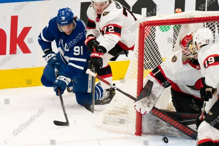 Toronto Maple Leafs center John Tavares(91) is checked by Ottawa Senators defenceman Thomas Chabot(72) as he gets the puck to the front of the net during an NHL hockey game, in Toronto, Canada