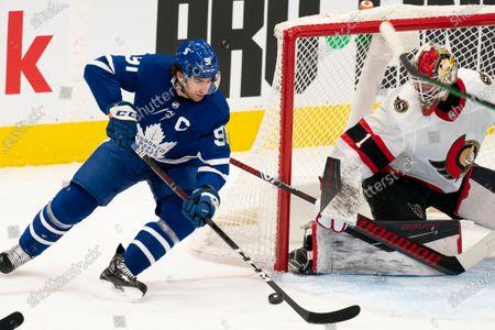 Stock Image of Toronto Maple Leafs center John Tavares(91) tries a wrap-around on Ottawa Senators goaltender Marcus Hogberg(1) during an NHL hockey game, in Toronto, Canada