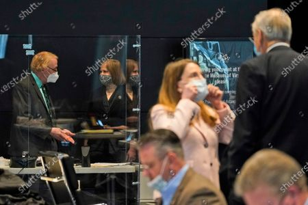 Virginia State Sen. George Barker, D-Fairfax, left, talks with Sen. Ghazala Hashmi, D-Chesterfield, second from left, during the Virginia Senate session at the Science Museum in Richmond, Va., . Barker is behind a protective enclosure due to health issues