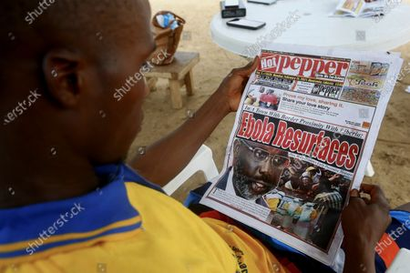 A Liberian man reads a newspaper reporting on the Ebola outbreak in neighbouring Guinea at a sidewalk news stand in Monrovia, Liberia, 16 February 2021.  According to a statement from the office of Liberian President George Weah on 14 February 2021 the president has placed Liberia's health authorities on an increased alert level following the death of four people from Ebola in neighbouring Guinea marking five years since the last cases were recorded.