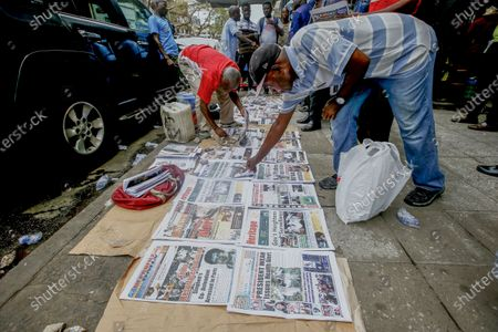 Stock Image of Liberian men look at newspaper headlines reporting on the Ebola outbreak in neighbouring Guinea at a sidewalk news stand in Monrovia, Liberia, 16 February 2021.  According to a statement from the office of Liberian President George Weah on 14 February 2021 the president has placed Liberia's health authorities on an increased alert level following the death of four people from Ebola in neighbouring Guinea marking five years since the last cases were recorded.