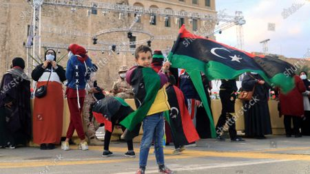 A boy holds a Libyan flag a day ahead of commemorations of the 10th anniversary of the uprising against former leader Muammar Gaddafi, in Tripoli, Libya, 16 February 2021. On 17 February 2011, a rebellion against the 42-year-long rule of the Libyan leader, Colonel Muammar Gaddafi took place. The protests began peacefully but soon escalated into a violent confrontation, giving the Libyan revolt a more bloody character than those in Tunisia and Egypt.  Gaddafi was captured alive on 20 October 2011 by National Transitional Council-backed fighters in Sirte and then killed along with his son, Moutassem. After years of political and security turmoil, a UN-led libya forum voted on the formation of a new government on 05 February 2021, the country is due to hold presidential and parliamentary election in December 2021.