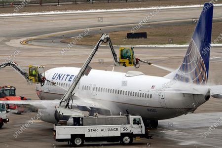 United Airlines jet is deiced at George Bush Intercontinental Airport, in Houston. Airport officials said crews are still working to clear thick patches of ice off of the airfield. They expect the airfield to open later this evening after being closed for days due to the severe cold weather which blanketed the area with snow and ice