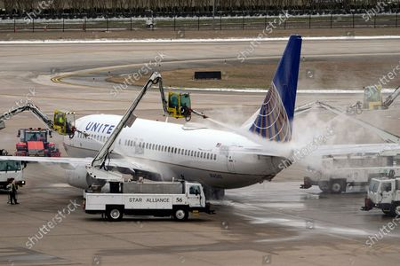 Stock Image of United Airlines jet is deiced at George Bush Intercontinental Airport, in Houston. Airport officials said crews are still working to clear thick patches of ice off of the airfield. They expect the airfield to open later this evening after being closed for days due to the severe cold weather which blanketed the area with snow and ice